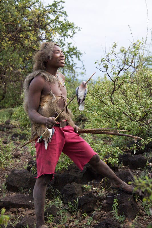 Hadzabe hunter laughing with bird on arrow