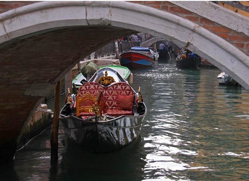 Venice gondola parked near bridge