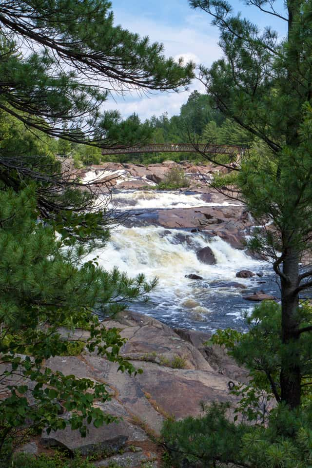 Onaping Falls and bridge seen through pine trees Onaping Ontario