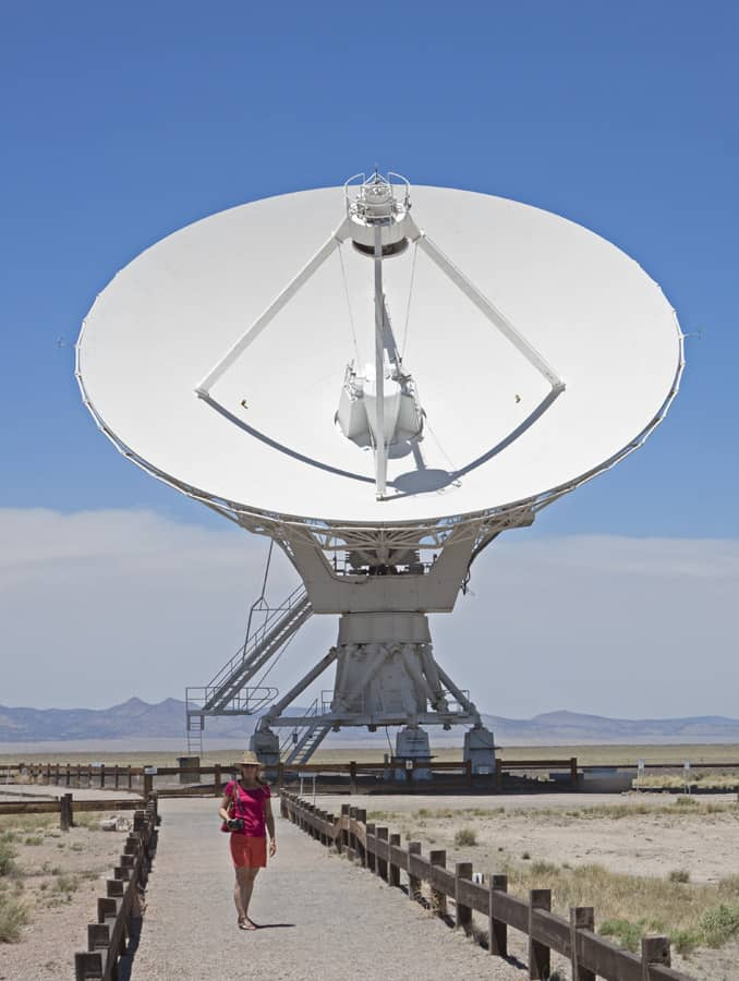 Giant radio telescopes at the VLA move along railroad tracks and turn in unison to follow signals.