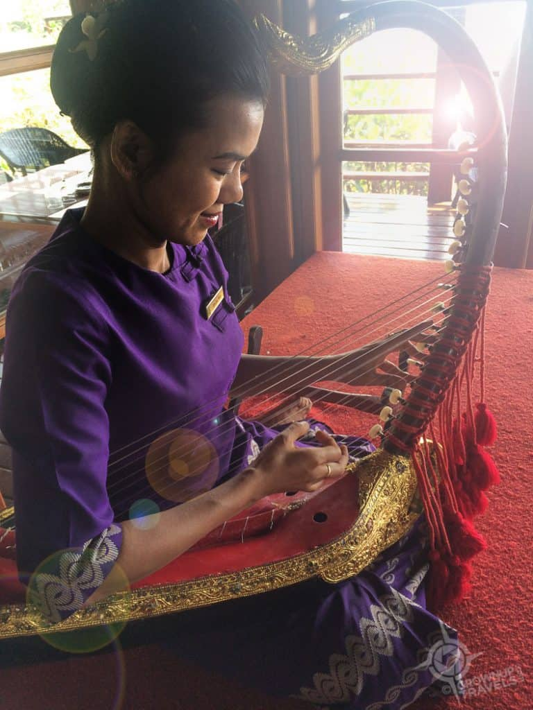 Burmese woman playing arched harp in Bagan